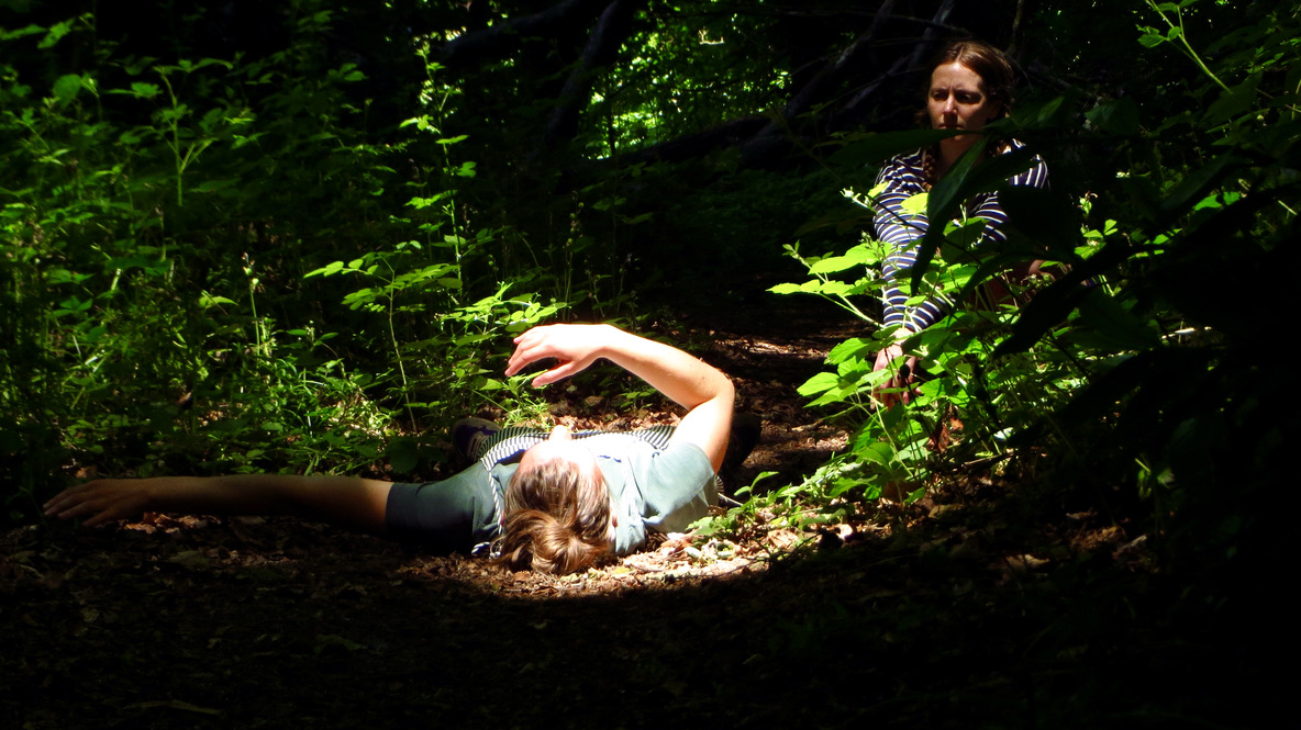 woman lying in a sun pool in the forest with an onlooking witness